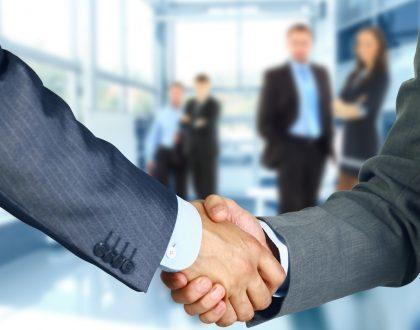 Website Design business associates shaking hands in office